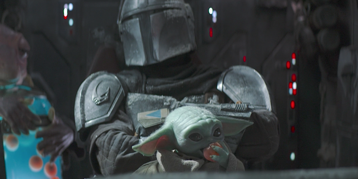 the mandalorian baby yoda held by mando and eating frog lady's egg