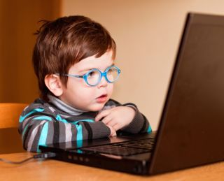 A young boy looks at a computer, wearing glasses