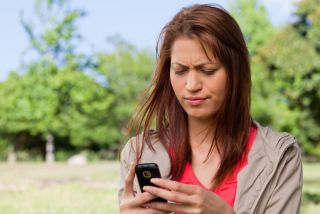 A woman looks confused as she reads a text message on her phone.