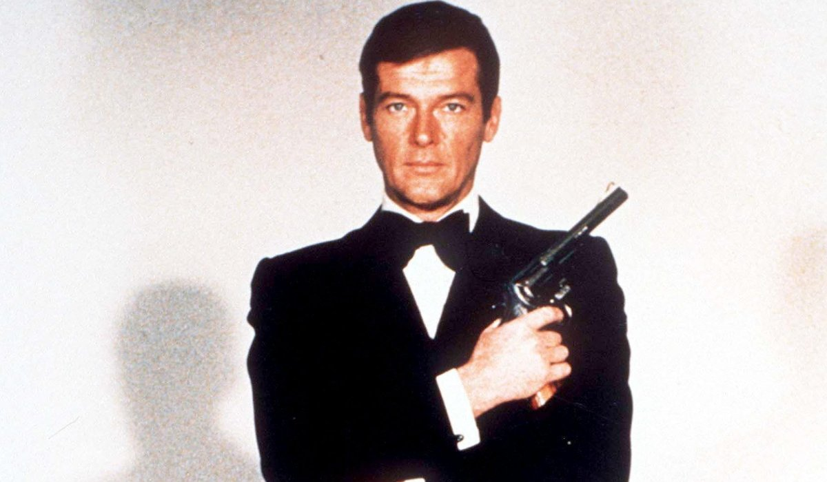 Roger Moore, posing in a tuxedo with a revolver