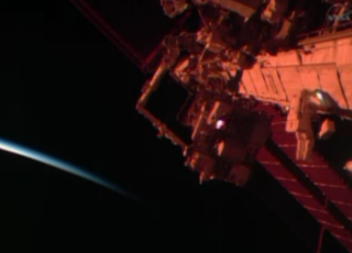 NASA astronaut Rick Mastracchio moves toward the International Space Station's robotic arm as the station moves into daylight on Dec. 24, 2013.