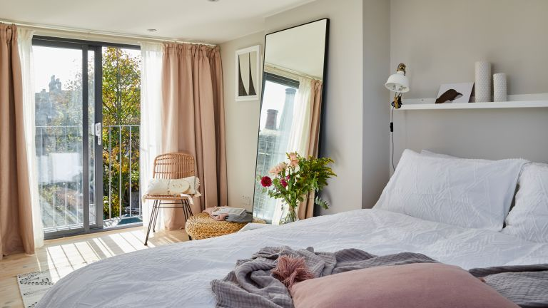 Pink drapes over sliding doors in bedroom with white bedding, full length mirror, rattan chair and greenery indoors