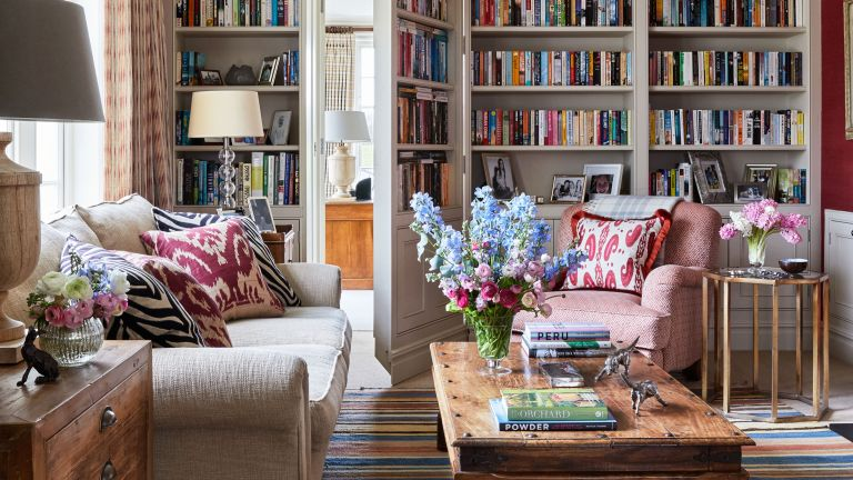 Small living room storage ideas with floor to ceiling built-in bookcase, colorful upholstery and fresh flowers
