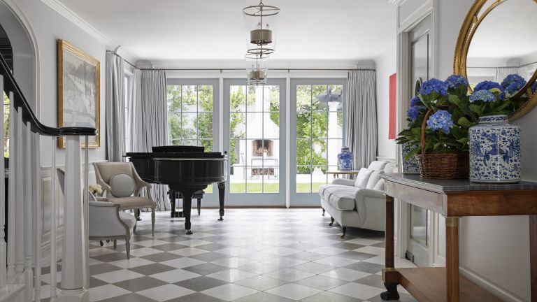 Hallway ideas featuring gray and white checkered floor, white walls, glass lighting, a pale sofa and black grand piano.