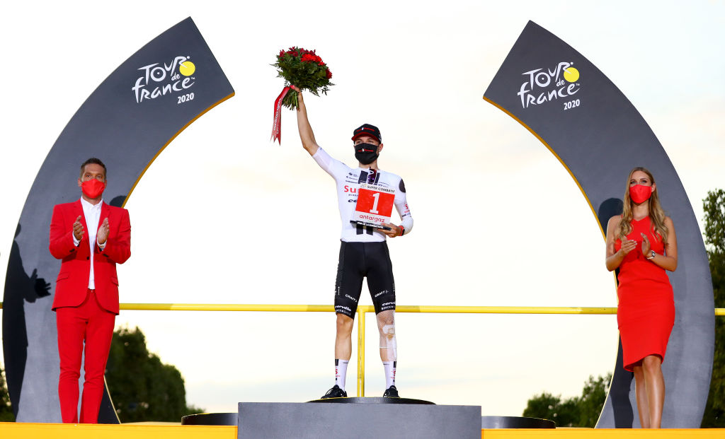 PARIS FRANCE SEPTEMBER 20 Podium Marc Hirschi of Switzerland and Team Sunweb Most Combative Rider Celebration Trophy Flowers Miss Hostess Mask Covid safety measures during the 107th Tour de France 2020 Stage 21 a 122km stage from MantesLaJolie to Paris Champslyses TDF2020 LeTour on September 20 2020 in Paris France Photo by Michael SteeleGetty Images