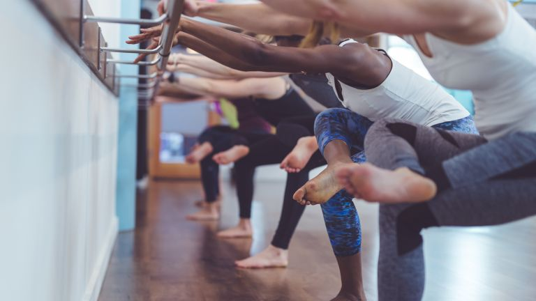 A group of people using a barre as they lean back into a stretch