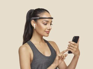 Woman wearing Muse 2 meditation headband uses touchphone.