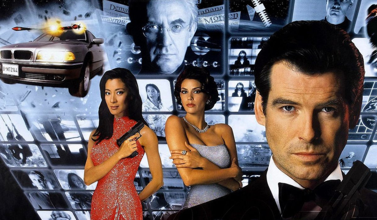 Tomorrow Never Dies Bond and his co-stars in front of a wall of monitors