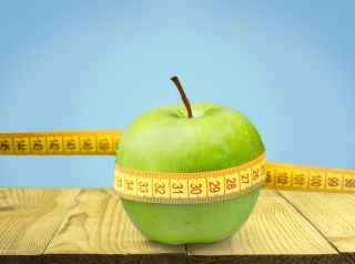 An apple, wound up in a measuring tape, to represent weight loss