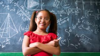 Smiling girl stands in front of blackboard filled with equations
