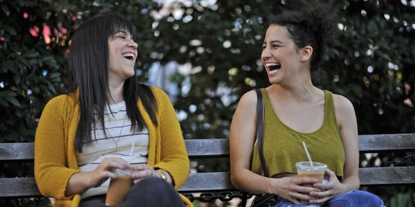Abbi and Ilana laughing on a bench