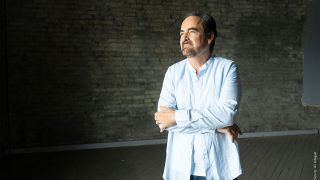 Neal Morse in a blue suit standing by a wall