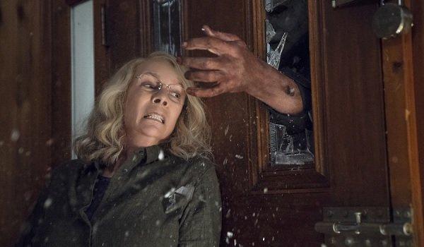 Halloween Jamie Lee Curtis trembles under Michael Myers' hand, bursting through the glass