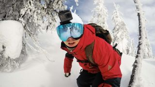 Man snowboarding with action camera attached to his helmet