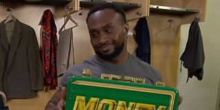 WWE's Big E smiles with the Money In The Bank case in the locker room.