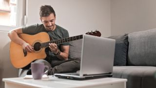 Young man playing acoustic guitar while sitting on a sofa in his living room.