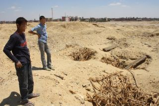 Two kids take a break at a heavily looted ancient cemetery at Abusir el-Malek, located south of Cairo.