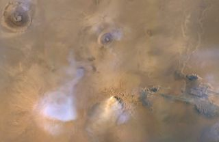 An image captured by NASA's Mars Reconnaissance Orbiter in 2010 shows a yellowish dust cloud with blueish-white plumes of water vapor.