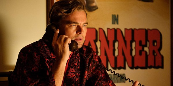 Once Upon A Time In Hollywood Rick takes a call in front of his poster