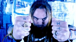 A photograph of Max Cavalera holding his fists up to the camera