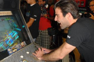 Zachary Quinto playing an arcade game