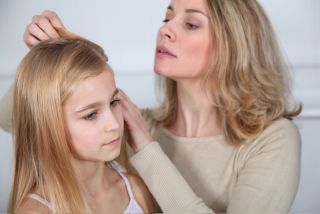 A mom fine-tooth combs her daughter's hair.