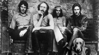 Derek And The Dominos sitting on a bench next to a wall with a dog at their feet