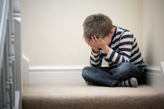 Upset problem child with head in hands sitting on staircase.