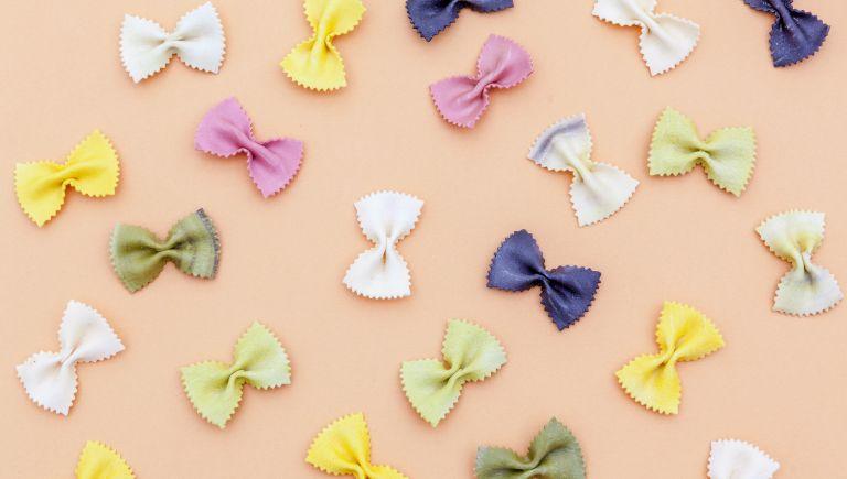 Farfalle pasta random flat lay pattern on color background