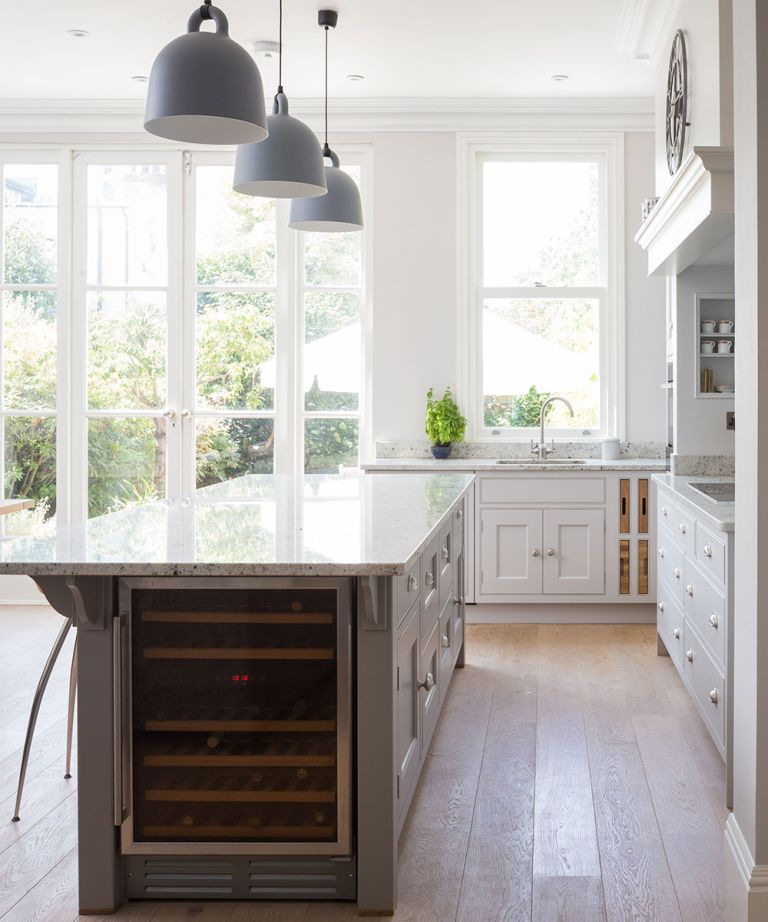 The future of kitchen design showing an open plan kitchen with marble worktops and an island with gray cabinets and a wine cooler