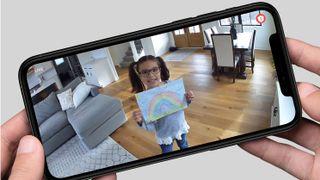 Person håller i mobil som visar bild från hemövervakningskameran.