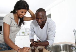 A man and a woman using a smartphone in the kitchen.