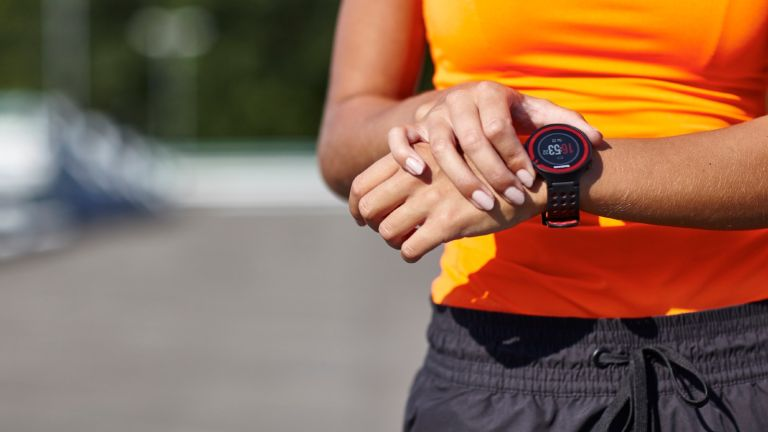 Best fitness trackers: woman checking fitness watch