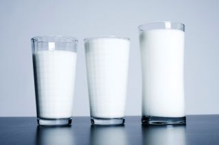 Three glasses of milk sit on a table.