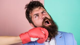 A man with a beard takes a punch to the jaw.