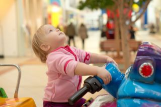 A small child rides on a ride at a mall
