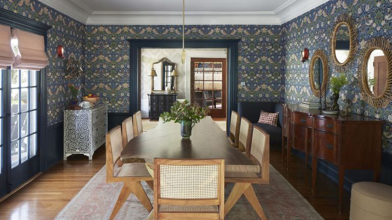 Dining room ideas with blue William Morris print wallpaper, large dark wooden sideboard and light wooden dining table with rattan chairs
