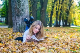 Girl with a book in an autumn park.