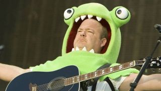 Kyle Gass of Tenacious D onstage dressed as a green monster