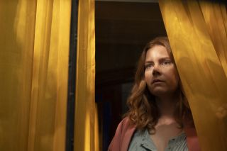 The Woman In The Window: Anna Fox (Amy Adams) stands in a darkened house, peering through a curtain