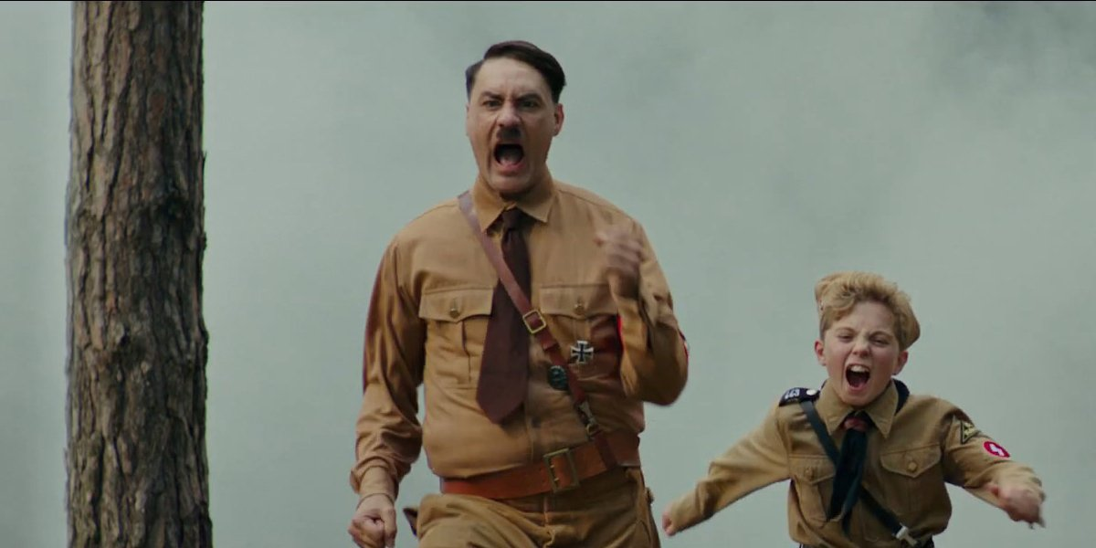 Taika Waititi as Hitler running with Roman Griffin Davis as Jojo in Jojo Rabbit