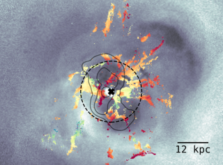 An image shows how galaxy-sized bubbles shove gas around in the Perseus galaxy cluster. The X at the center of the image shows the location of the supermassive black hole at its center.
