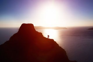 A man climbs a coastal mountain