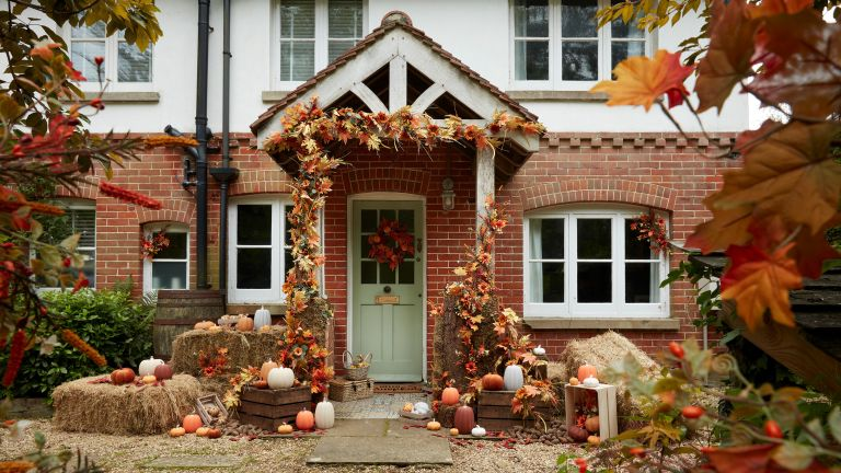 House decorated for Halloween with autumn wreath, pumpkins and baskets