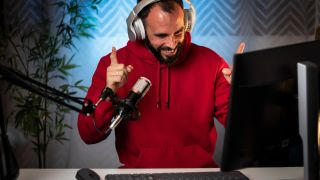 Man in red top smiles while recording a podcast