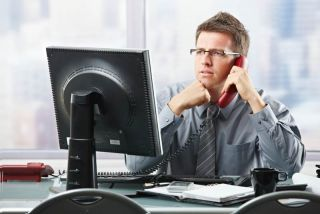 man sitting at desk and talking on the phone.
