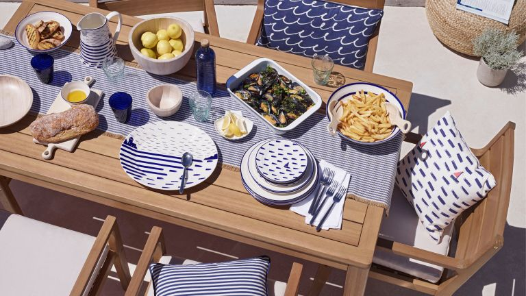 wooden table with blue throw and tablke scheme for outdoor dining