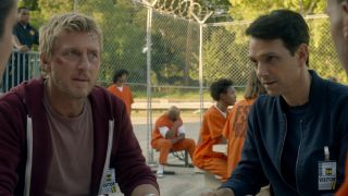 Johnny Lawrence and Daniel LaRusso at a table in a prison in Cobra Kai, which returns to Netflix in 2021.