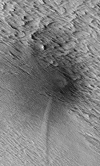 This HiRISE image from NASA's Mars Reconnaissance Orbiter shows a central crater on Mars with two dagger-like features extending at an angle. Called scimitars, these features most likely resulted from shockwave interference just before impact, scientists