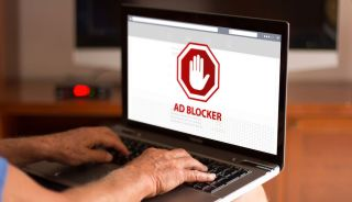 A man's hands type on a laptop with the words 'Ad Blocker' displayed on the screen.